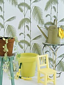 Chair, watering can and gardening tools in front of patterned wallpaper