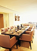 Long set dining table and armchairs in pale dining room