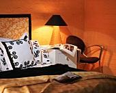 Warm light from lit bedside table in orange bedroom