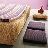 Wicker lounger with mattress, two floor cushions and glass carafe on small wicker table