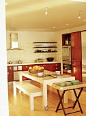 White dining table on castors and matching benches in modern kitchen