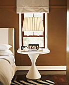 Round, white bedside table below sixties-style lamp next to bed