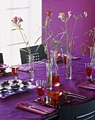 Gedeckter Tisch mit lila Tischdecke und Sommerblumendeko