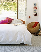 Bed in front of open terrace door; round rattan chair in corner and objets d'art on wall