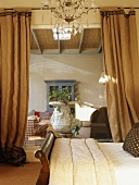 Bedroom with chandelier and view into living room between two heavy curtains