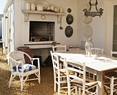 Sunny terrace with open fireplace, rustic dining table, simple rush-seat chairs and one white wicker chair
