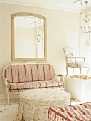Delicate, Biedermeier-style couch with striped upholstery below framed mirror; Baroque chair on pedestal