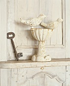 Rustic key and birdbath on cabinet