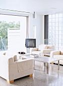 Sofagarnitur und alter Fernseher vor Glasstein-Fenster