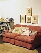 Rote Couch mit geblümte Kissen unter Blumenbilder an der Wand