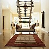 Blick auf Tagesliege unter Treppe mit hinunter steigende Frau