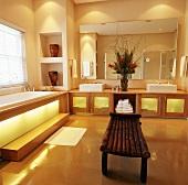 Badewanne unter Fenster und zwei Waschbecken unter großen Spiegel im Badezimmer mit beleuchteren Schranktüren und rustikaler Holzbank