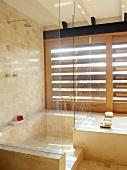 Transparente Duschkabine neben Badewanne vor Fensterläden aus Holz im mediterranem Bad
