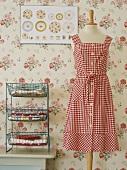 Verschiedene Stoffe und weiß-rot kariertes Kleid an Schneidepuppe vor geblümte Wandtapete