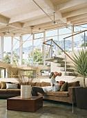Mann und Baby auf braune Eckcouch im offenem Wohnraum mit Panoramafenster und Holzbalkendecke