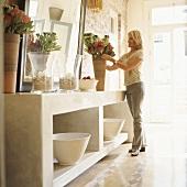 Eine Frau drappiert ein Blumenarrangement an einem steinernen Wandtisch