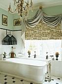Prunkvolles Badezimmer mit edlem Kronleuchter und dekorativ drappiertem Store