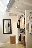 Blick in ein Ankleidezimmer mit offenen Kleiderstangen unter verglaster Dachkonstruktion
