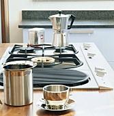 Ein Kaffeekocher auf dem Gasherd, im Vordergrund eine Tasse aus Metall und eine Milchkanne