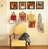 Eine Gemäldeserie und verschiedene Taschen über einem antiken Stuhl