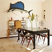 Table, chairs, console cabinet & ornaments on walls