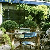 Gartentisch mit Klappstühlen und offenes Buch vor Backsteinhaus