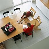 Aufsicht von einem Esstisch mit zwei malenden Kindern und einer Katze