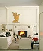 Galeriewohnung mit weißer Couchgarnitur vor Kamin aus Backstein
