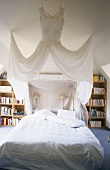 A four-poster bed and book case