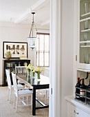 Dunkel brauner Esstisch mit weißen Stühlen im hellen Fachwerkhaus