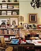 Ein vollgestelltes Arbeitszimmer mit vielen Büchern und Familienfotos