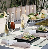 An oriental-style table laid with rice paper rolls