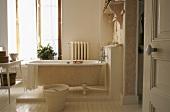 Eine freistehende Badewanne auf Podest im hellen Badezimmer mit Tageslicht