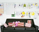 Schwarze Ledercouch mit Stofftier und bunte Kissen unter hängenden Kinderzeichnungen