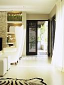 Modernes Wohnzimmer mit zwei große weiße Sessel und Tierfell auf dem Boden