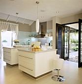Moderne Küche mit zwei Kochblöcken vor offenen Terrassentüren