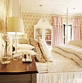 Romantic bedroom with floral wallpaper, bed & bedside cabinet