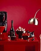 Erdbeeren und Sekt auf rotem Tisch
