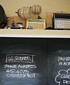 Phone numbers on blackboard below shelf