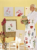 Woman holding vase in front of floral artworks