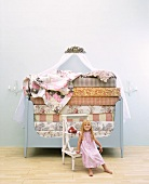 Little girl sitting in front of bed stacked high with mattresses