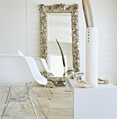 Two designer chairs and mirror on wall