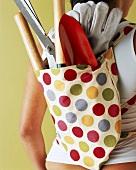 Frau mit Gartengeräten im Rucksack