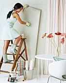 Young woman hanging wallpaper
