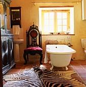 Zebra-skin rug in front of free-standing bathtub