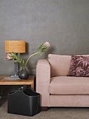 Couch and table lamp against grey wall