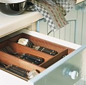 Open cutlery drawer in kitchen