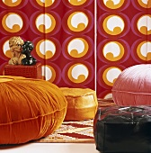 Various floor cushions in front of colourful wallpaper