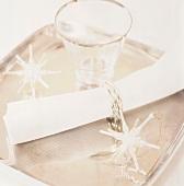 Gerollte Serviette, Glas und Sterne auf einem Tablett