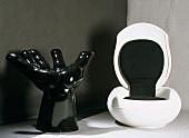 Stuhl in Handform und weisser Klappstuhl